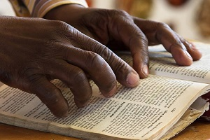 Marc-Ewell-African-hands-reading-Bible